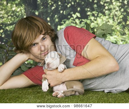 A teen boy cuddling his sleeping pitbull pup while relaxing on the lawn.