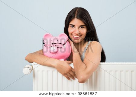 Woman With Piggybank And Radiator