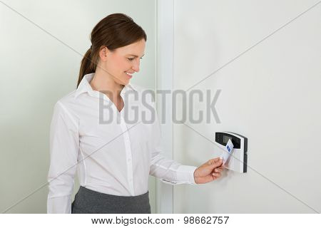 Businesswoman Inserting Keycard In Security System