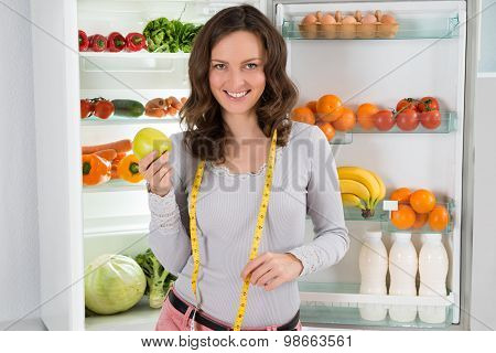 Woman With Measuring Tape And Apple Near The Refrigerator