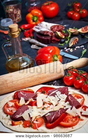 Raw pizza with parmigiano and proscuitto