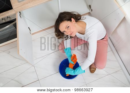 Woman Squeezing Fabric In Bucket