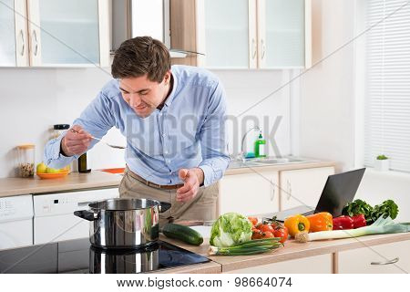 Man Tasting Meal In Kitchen