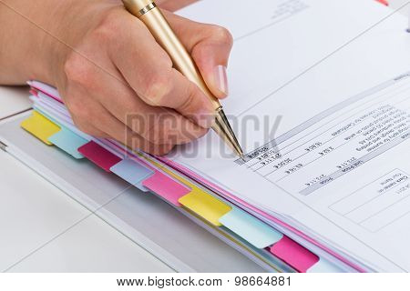 Person Hands With Pen Over Invoice