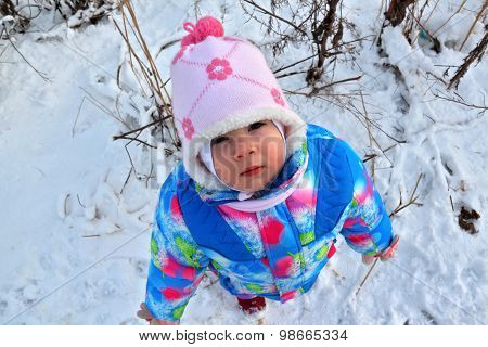 Small Child Looks Up At Winter Snowy Landscape