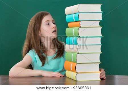 Girl Looking At Stack Of Books