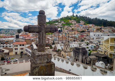 Stone cross decoration belonging to San Diego church with beautiful view showing old part of Quito b