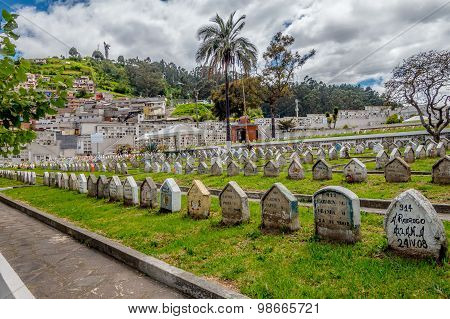 Row of gravestones on grass in cemetary San Diego church historical part Quito with spectacular view