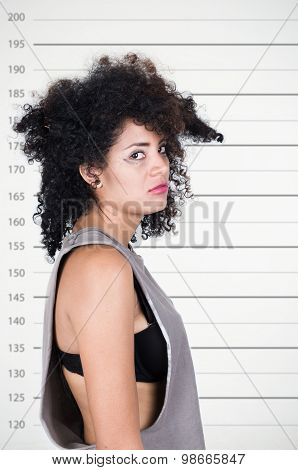 Hispanic brunette model with messy hair wearing grey sleeveless shirt looking unhappy into camera fr