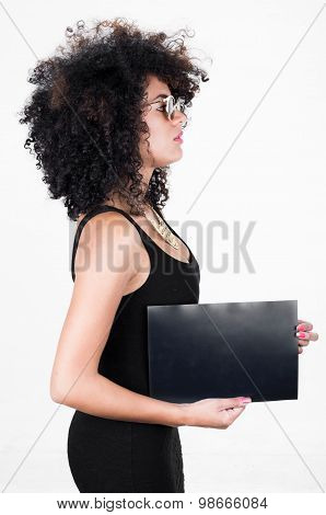 Hispanic model wearing black sexy dress and sunglasses holding blank board posing from profile angle