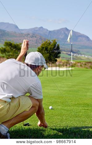 aiming golfer lining putt on green