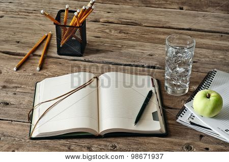 blank diary on wooden table with a glass of water, apple and pencil closeup.