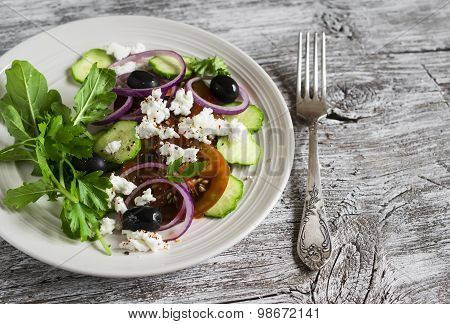 Greek Salad - Salad With Tomatoes, Cucumbers, Olives And Feta Cheese On A White Plate On A Light Woo