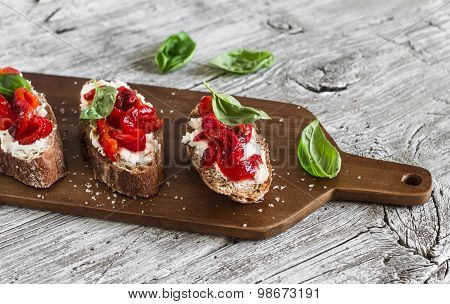Bruschetta - Rye Baguette, Feta Cheese, Roasted Peppers And Basil On A Light Wooden Surface
