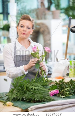 Portrait of florist making rose bouquet at counter in flower shop
