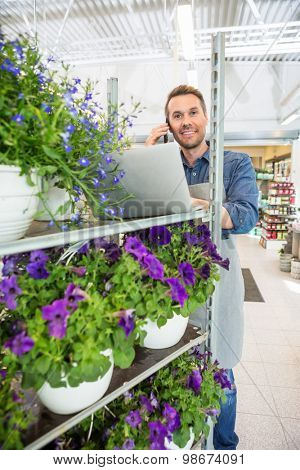 Portrait of male florist using mobile phone and laptop in flower shop