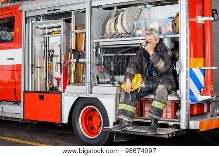 Full length of fireman drinking coffee while sitting in truck at fire station