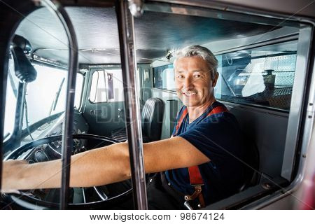 Portrait of happy mature fireman driving firetruck at station