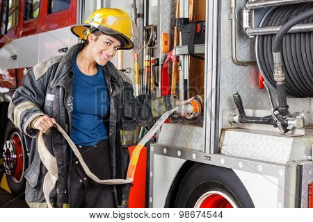 Portrait of happy female firefighter adjusting water hose in truck at fire station