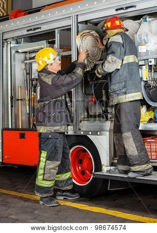 Full length of male firefighters removing hose from truck in fire station