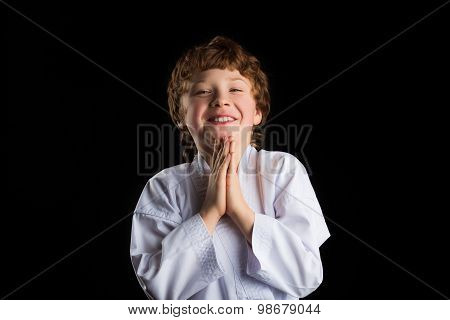 Smiling karate boy in white kimono isolated on black background
