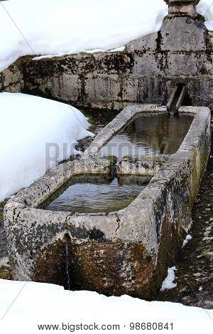 Stone Fountain With Freezing Cold Water In Winter