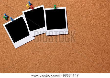 Three Blank Photos Pinned To A Cork Board
