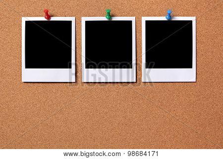 Three Blank Photos Pinned To A Cork Board