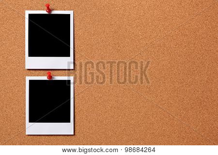 Two Blank Photos Pinned To A Cork Board