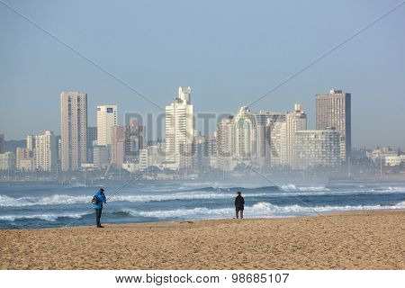 Two Fishermen On Durban Beach With Hotels In Background