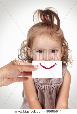 Happy Joyful Baby Girl Hiding Her Face By Hand With Smile And Teeth Drawn On Paper