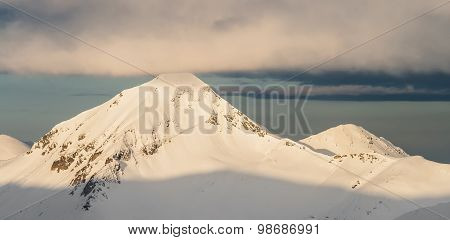 Sunlight Over Snowcapped Mountain Peak at Sunrise in the winter with clouds in the sky