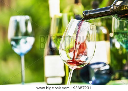Red wine on a background of colored bottles