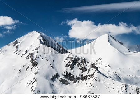 Two Pyramid Shaped Snowcapped Mountain Peaks