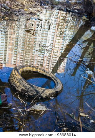Garbage, Old Tire And Reflection Of The High-rise In The Water
