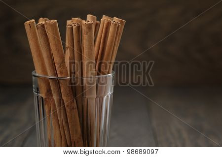 true cinnamon sticks in glass on wooden table, selective