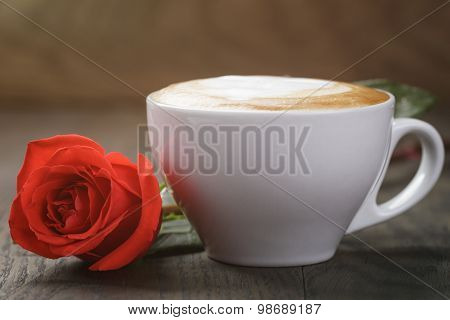 fresh cappuccino with red rose on wood table