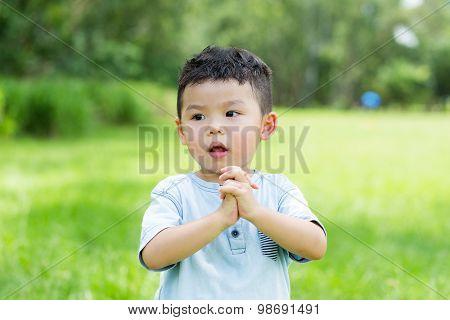 Little boy showing pray gesture
