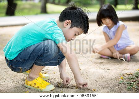 Little Asian Child Playing Sand In The Park