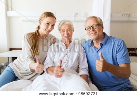 medicine, family support, gesture, health care and people concept - happy senior man and young woman visiting her grandmother and showing thumbs up at hospital ward