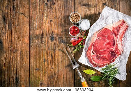 Raw fresh meat rib eye steak and seasoning on dark background