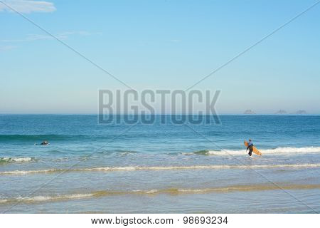 People Surfing In A Tropical Beach