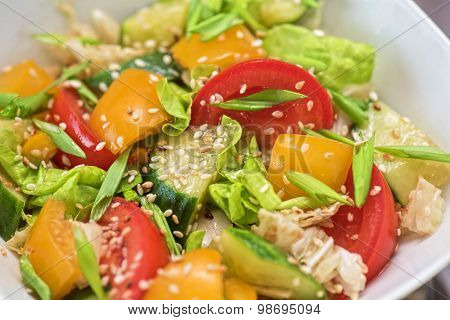 Bulgarian salad from pepper, cucumbers, tomato, green onion with sesame and oil