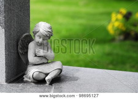Antique marble statue of a Cherub angel sitting on stone