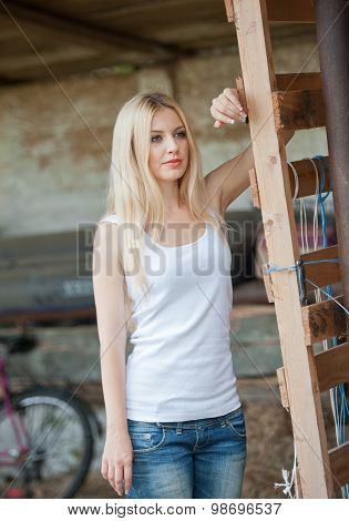 Shot of beautiful girl near an old wooden fence. Stylish look wear: white basic top, denim jeans