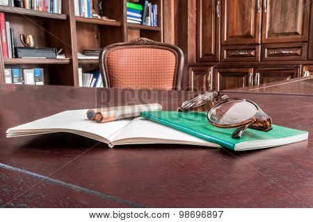 Set Of Notebooks On Desk With Pencils And Glasses