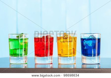 Various alcoholic cocktails on a bar counter with wooden background