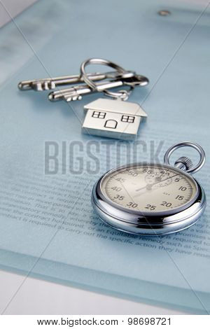 loan document ,stop watch and house shaped key chain with keys
