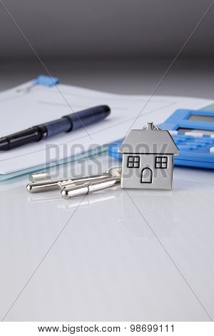 House shaped key chain with keys and calculator