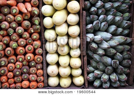 A display of carrots, white aubergines and green bananas for sale at a Sri Lankan market.